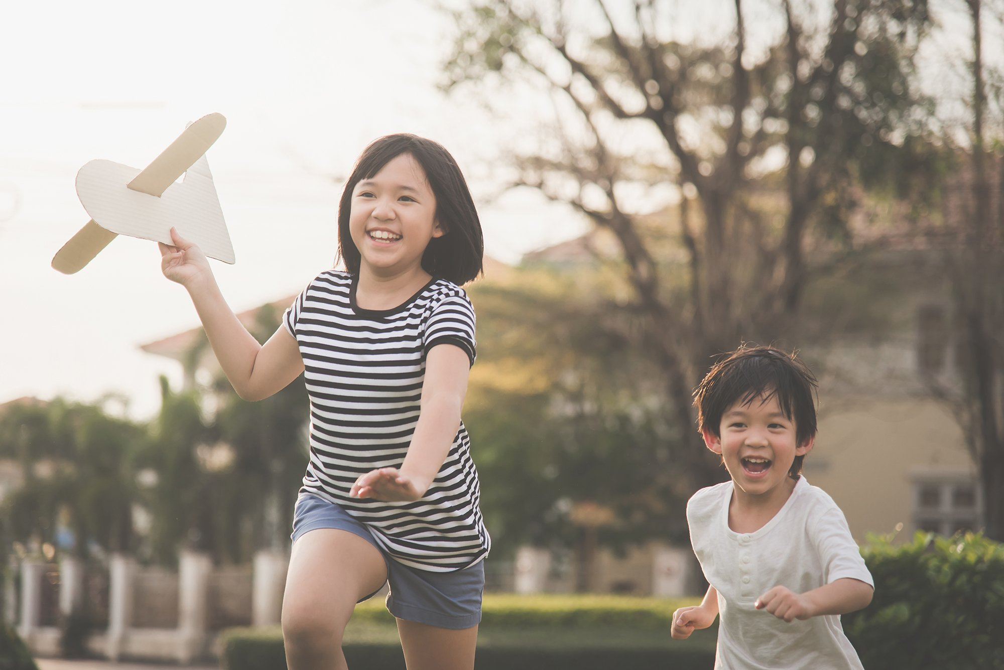 kids playing outside with paper airplane